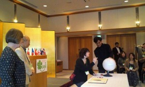 Hiroshi Doi and Jean Jones watch Audrey Pearson sign the globe as representative of the USA